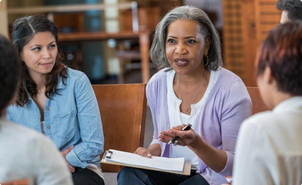A clinician facilitates group therapy.