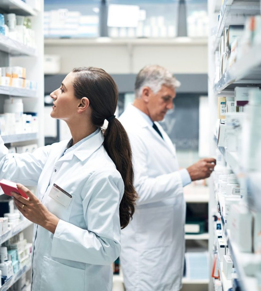 Two pharmacists browse for the suitable medication in a pharmacy aisle.