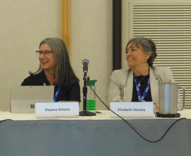Three panelists laugh seated behind name tags, pitchers of water, tablets, and microphones